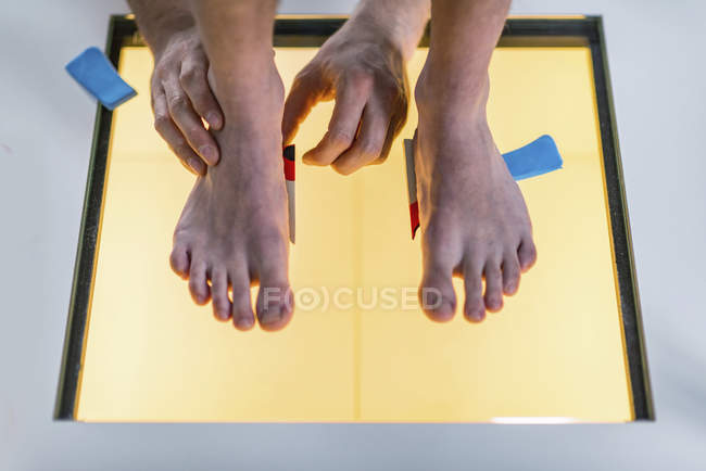 Physical therapist performing foot pressure scan for child. - foto de stock