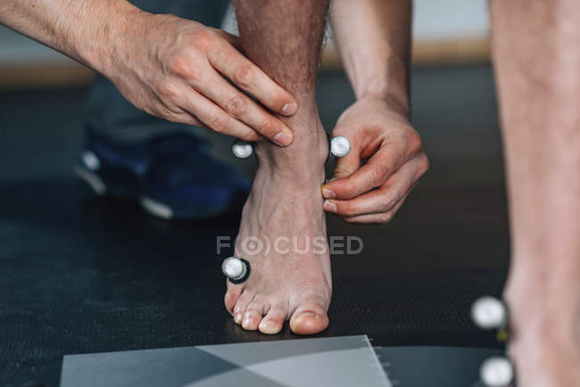 Physical therapist placing reflective marking balls on boy feet for gait analysis. — Stock Photo