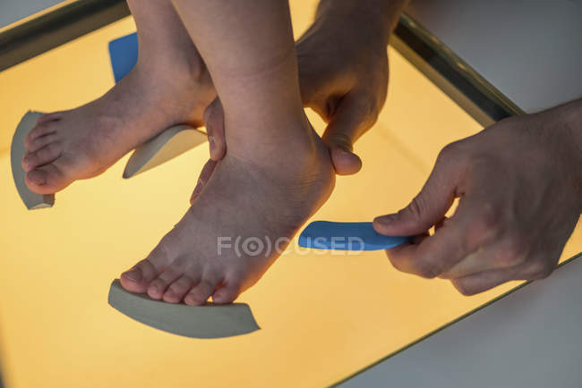 Physical therapist performing foot pressure scan for child. — Stock Photo
