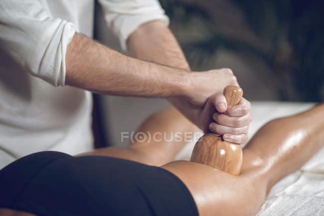 Primer plano del masajista masculino utilizando una herramienta de madera en la mujer mientras que la maderoterapia anti-celulitis . - foto de stock