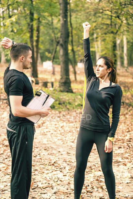 Женщина, работающая с группой сопротивления и инструктором по фитнесу, объясняет тренировку трицепса . — стоковое фото