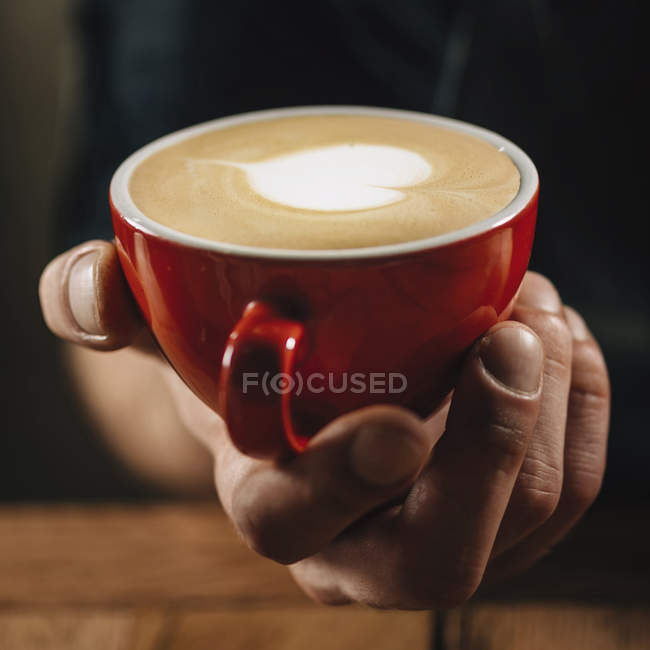 Professional barista holding in hand red coffee cup with heart latte art surface. — стокове фото
