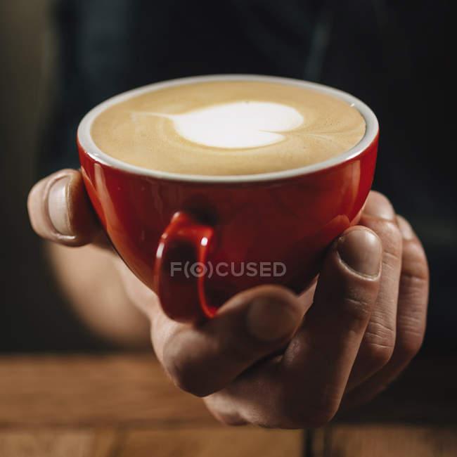Профессиональная бариста держит в руке красную чашку кофе с искусством латте сердца . — стоковое фото