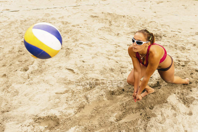 Female beach volleyball player in action with ball. — Stock Photo