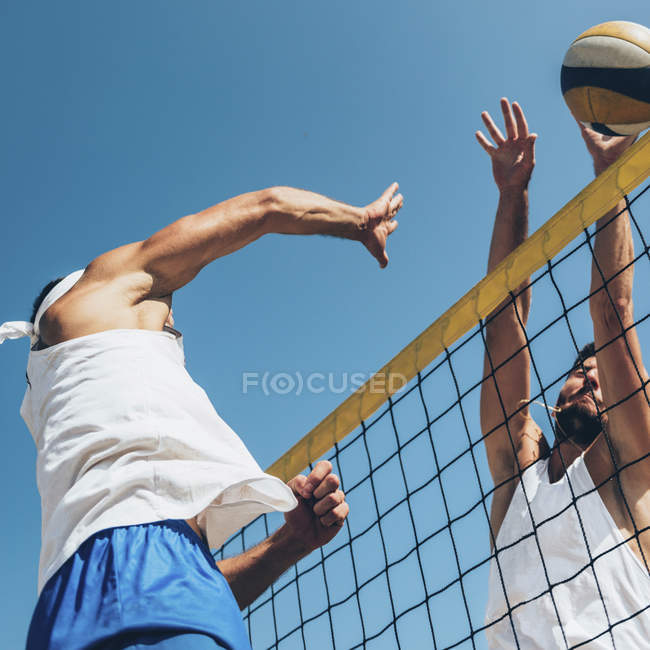 Low angle view of beach volleyball players hitting ball at net. — Stock Photo