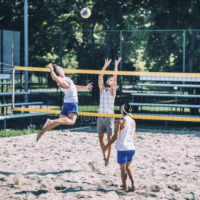 Пляжные волейболисты бьют и блокируют мяч в сетку во время игры . — стоковое фото