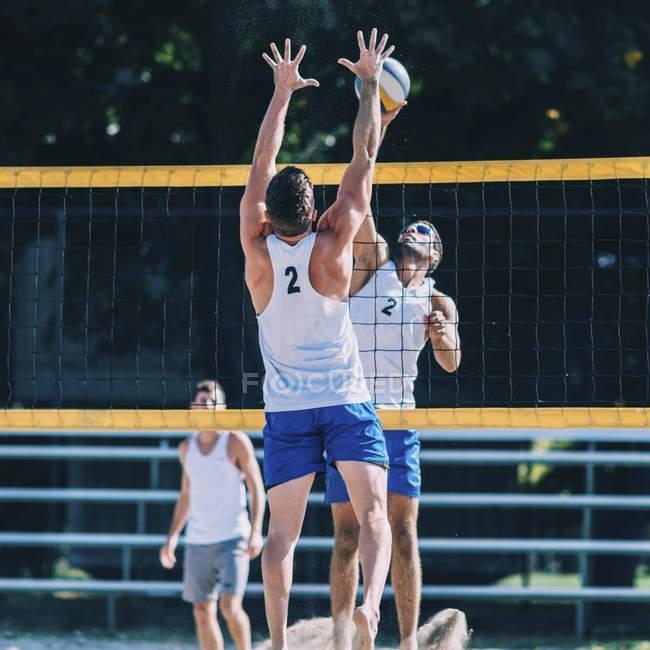 Игроки в пляжный волейбол блокируют сетку во время игры . — стоковое фото