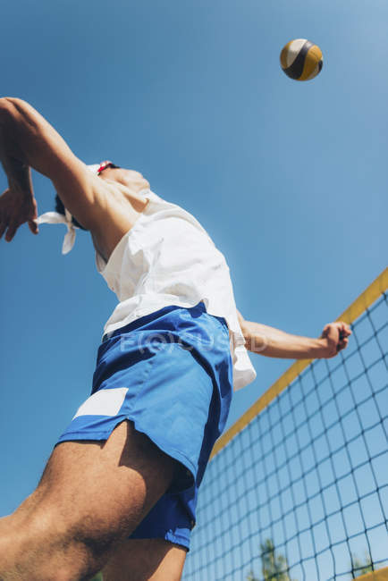 Low angle view of beach volleyball player jumping for ball at net. — Stock Photo