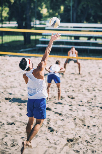 Male beach volleyball players in action with ball at net. — Stock Photo