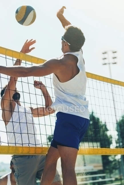 Male beach volleyball players jumping and hitting ball. — Stock Photo