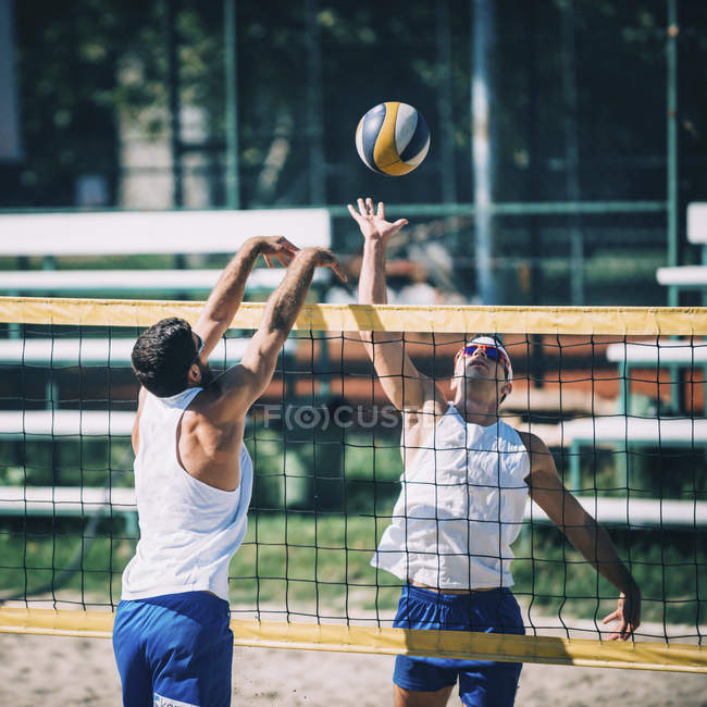 Beach volleyball players in action with ball at net. — Stock Photo