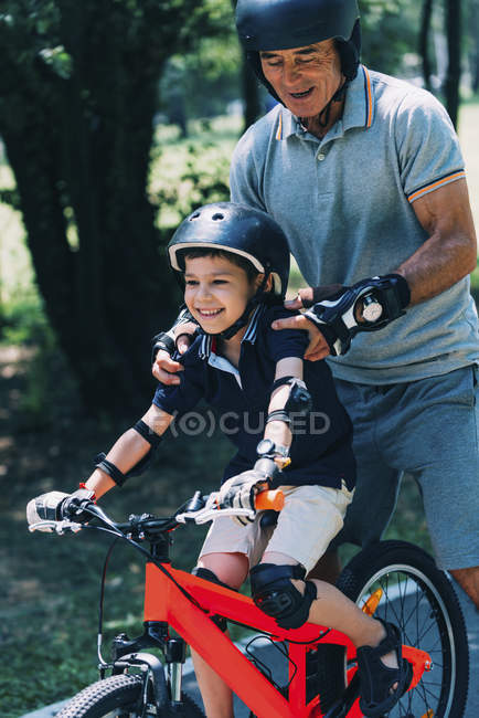 Grandfather and grandson enjoying biking in summer park. — Stock Photo