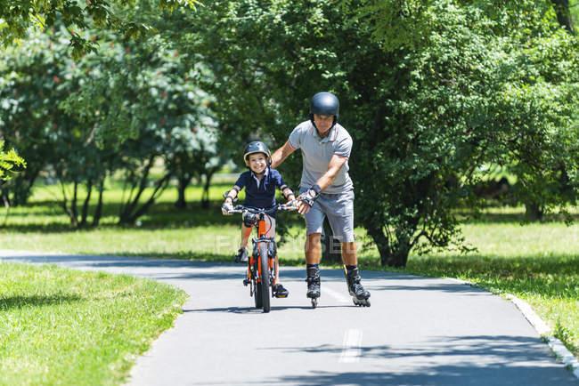 Sénior ativo em patins ensinando neto andar de bicicleta no parque . — Fotografia de Stock