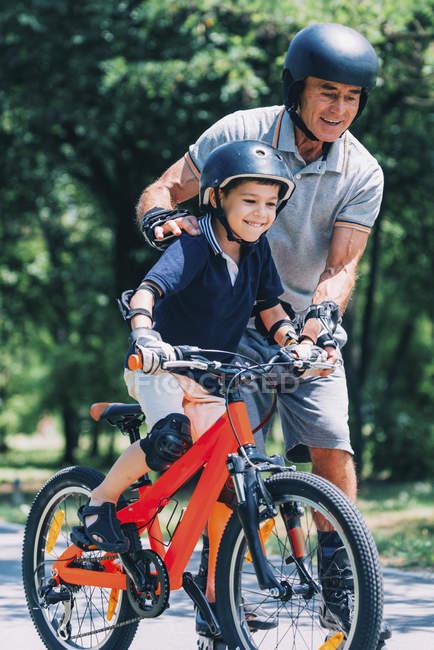 Avô e neto andando juntos em patins e bicicleta no parque . — Fotografia de Stock
