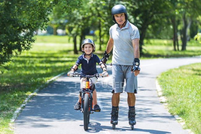 Дід і онук користуються велосипеді в літньому парку. — стокове фото