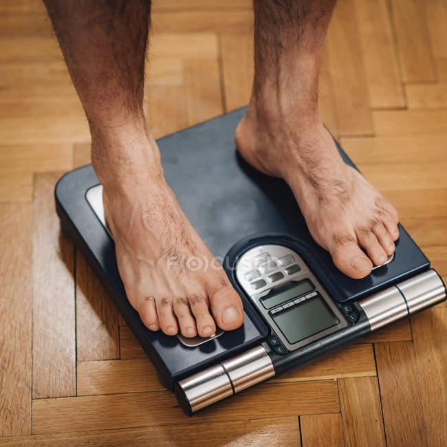 Pies de atleta masculino que mide la composición corporal con escala de suelo . - foto de stock