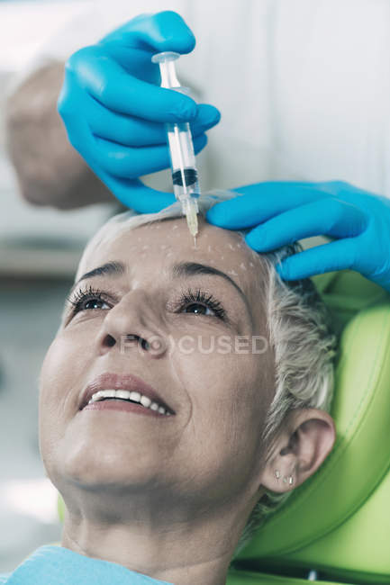 Mature woman receiving botox injection in forehead in cosmetology clinic. — Stock Photo