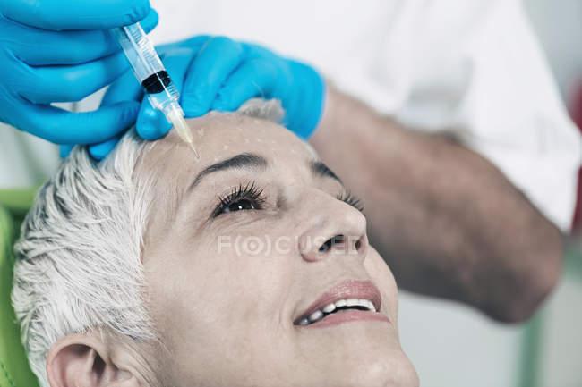 Femme mûr recevant l'injection de botox dans le front dans la clinique de cosmétologie. — Photo de stock