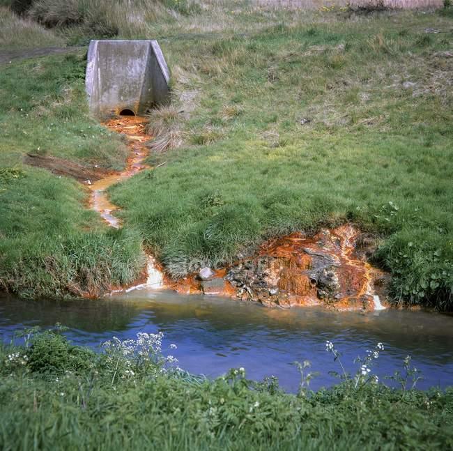 Agua contaminada químicamente que drena en el río Tame fuera de la tierra con desechos que contienen metales pesados, West Midlands, Reino Unido . - foto de stock