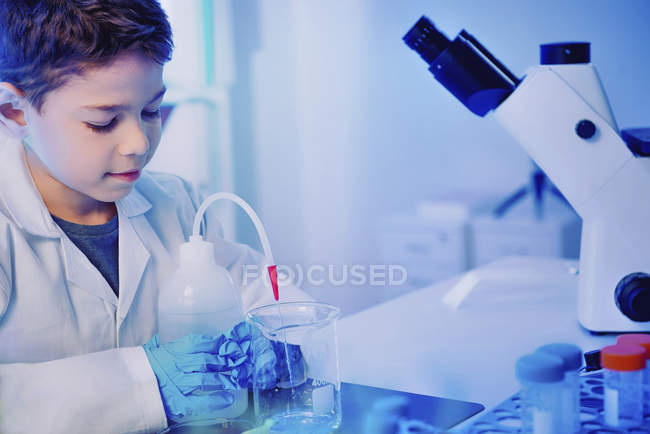 Schoolboy using glassware and equipment in school laboratory. — Stock Photo