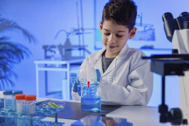 Schoolboy doing science experiment in school chemistry laboratory. — Stock Photo