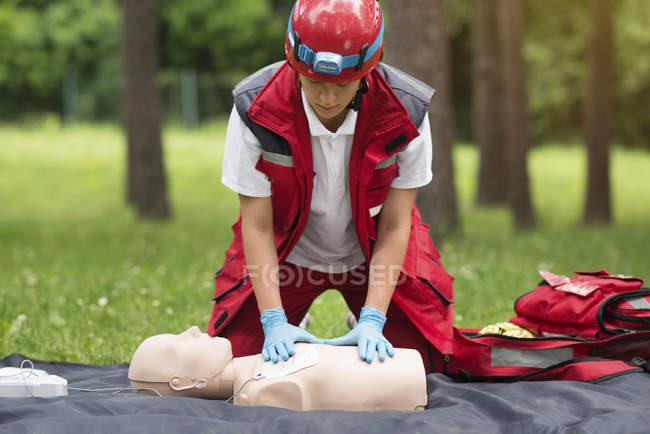 Treinamento de RCP paramédica feminina com manequim ao ar livre . — Fotografia de Stock