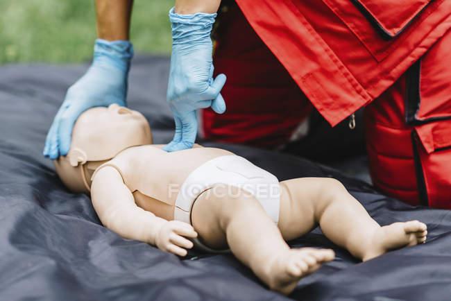 Mãos de treinamento de RCP paramédica feminina em boneco de bebê ao ar livre . — Fotografia de Stock
