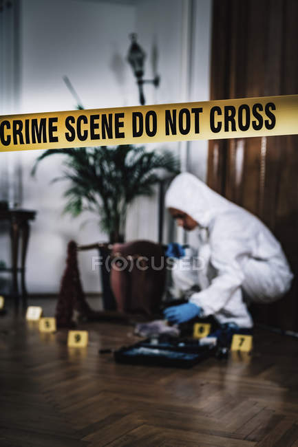 Forensics expert collecting evidence from crime scene behind cordon tape. — Stock Photo