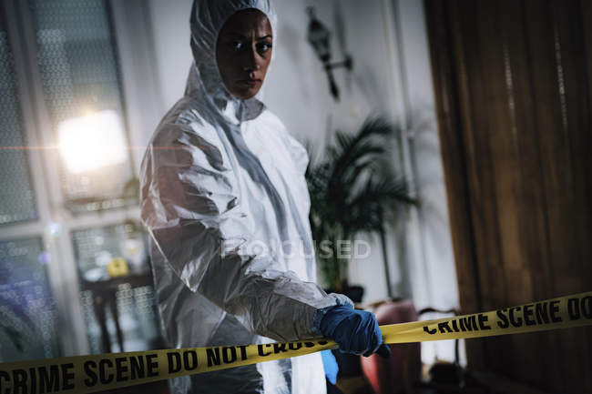 Forensics expert crossing cordon tape at crime scene. — Stock Photo
