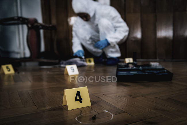 Crime scene markers and forensics expert collecting blood sample in background. — Stock Photo