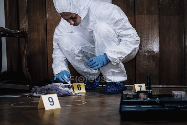 Forensics expert collecting blood sample from crime scene. — Stock Photo