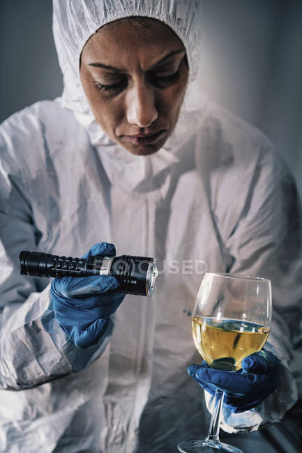Forensics expert examining with flashlight evidence glass of wine at crime scene. — Stock Photo