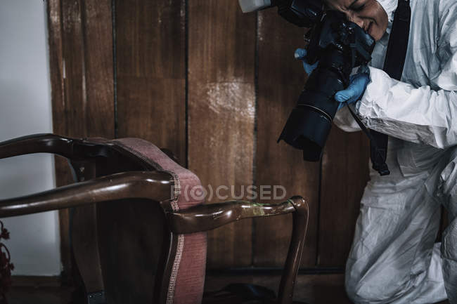 Forensics expert photographing evidence at crime scene. — Stock Photo