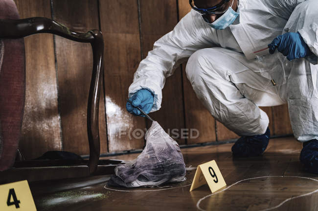 Forensics expert collecting evidence cloth from crime scene. — Stock Photo