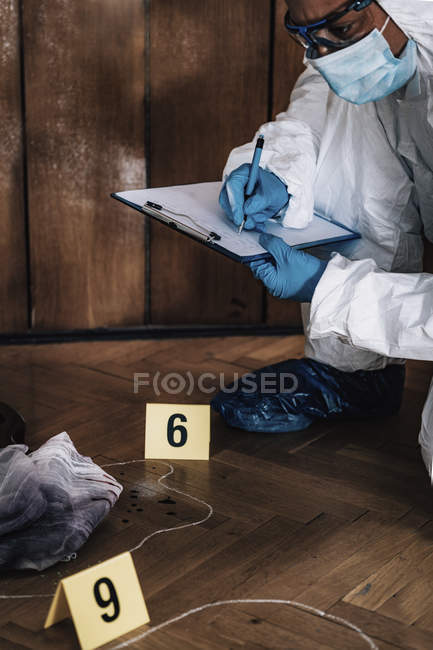 Forensics expert in protective suit writing in clipboard collecting evidence from crime scene. — Stock Photo