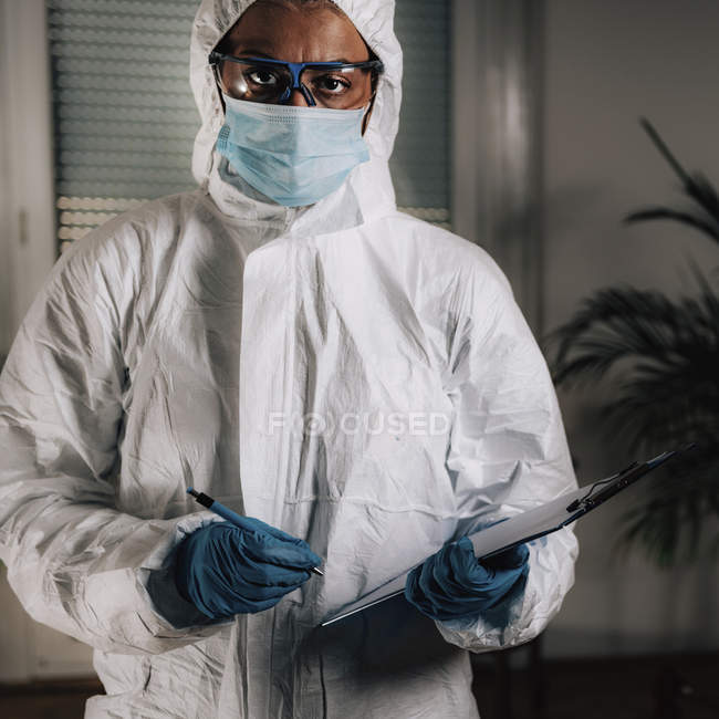 Forensics expert in protective suit writing in clipboard while examining crime scene. — Stock Photo