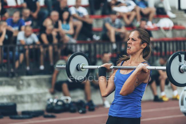 Юная спортсменка, принимающая участие в соревнованиях по тяжелой атлетике . — стоковое фото