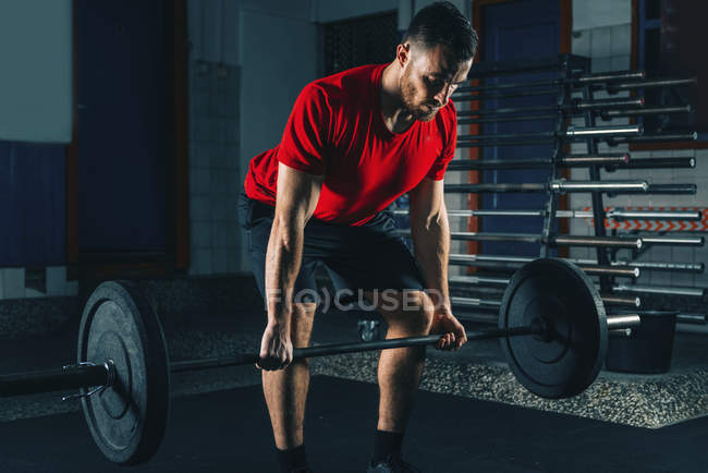 Muscular man in red t-shirt lifting weights in gym. — Stock Photo