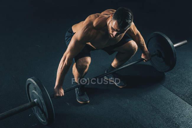 Muscular shirtless man lifting weights in gym. — Stock Photo