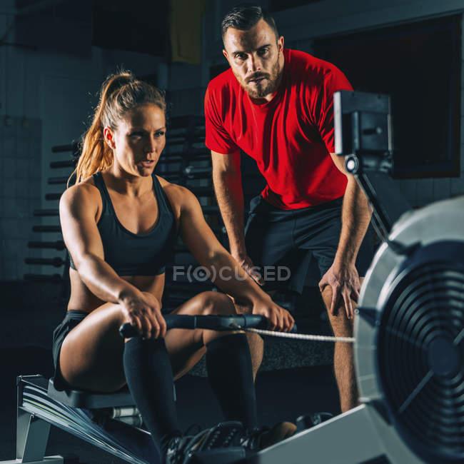 Fit женщина с мужчиной инструктор выполнения гребной тренажерный зал машины . — стоковое фото