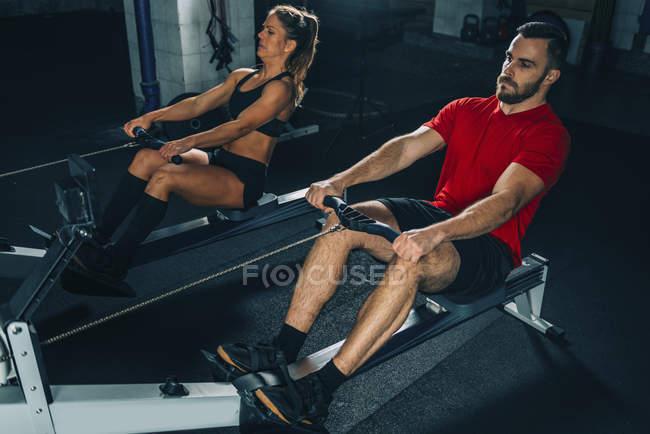 Подходят женщина и мужчина, выполняющие упражнения на роторных машинах в спортзале . — стоковое фото