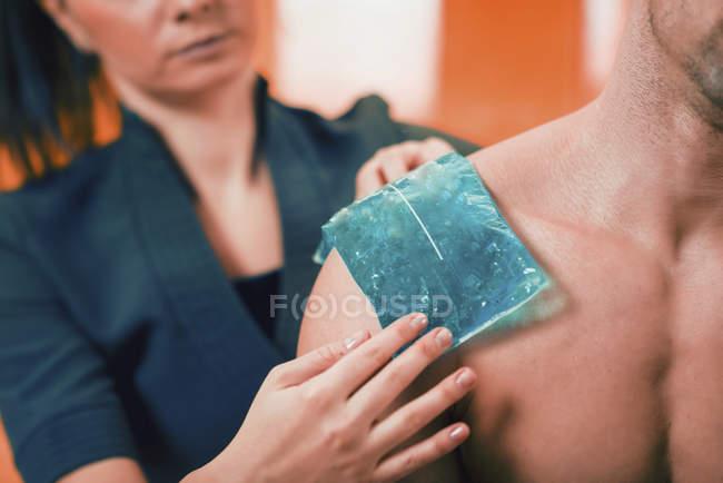 Terapeuta femenina aplicando compresa de hielo en el hombro doloroso del atleta masculino . - foto de stock