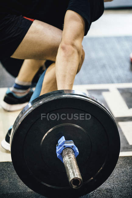 Cropped view of man weightlifting with barbell in gym. — Stock Photo