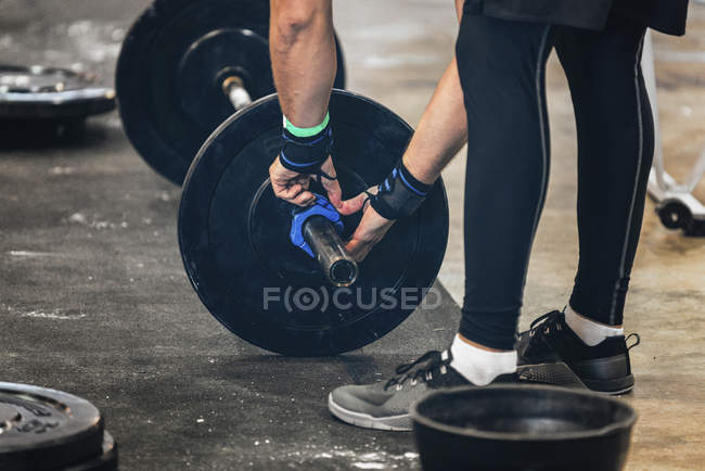 Cropped view of male athlete changing weights on barbell. — Stock Photo