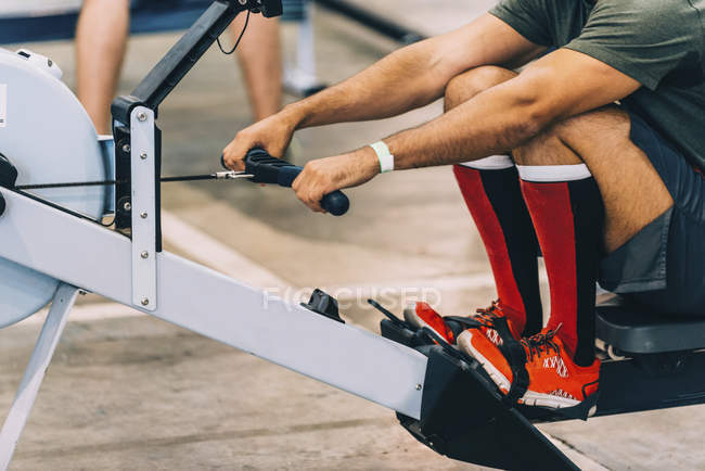 Cropped view of man in rowing machine workout. — Stockfoto