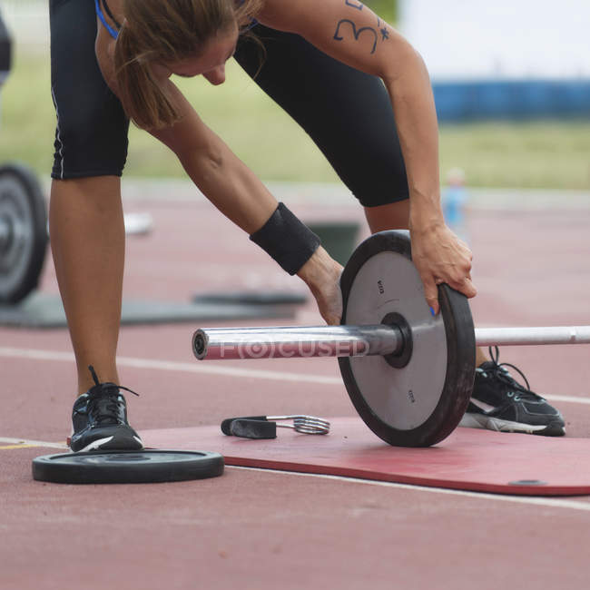 Bending female athlete changing weights on barbell at stadium. — Stock Photo
