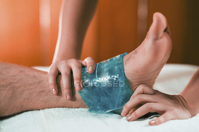 Hands of female therapist putting ice pack on painful ankle of male athlete. — Stockfoto