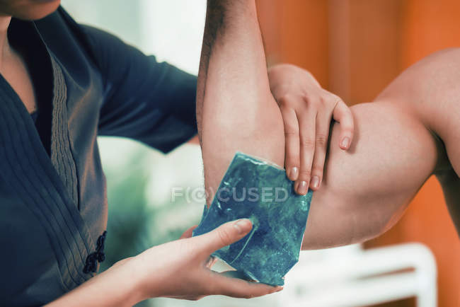 Female therapist putting ice pack on painful elbow of male athlete. — Fotografia de Stock