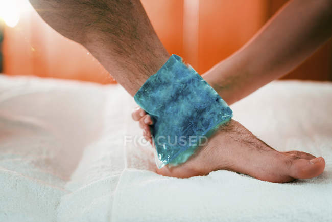 Mano de terapeuta femenina poniendo bolsa de hielo en el tobillo doloroso de atleta masculino . - foto de stock