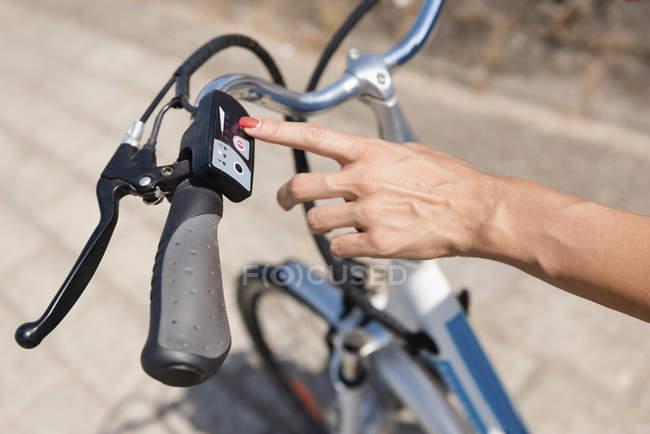 Рука женщины включает электрический велосипед, крупным планом . — стоковое фото